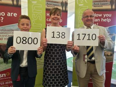 Trustees Della Armstrong, with son Ross, and our Agricultural Chaplain Rev Canon Alan Robson display the new Helpline number at an LRSN breakfast event, hosted by Brown and Co at the Lincolnshire Show